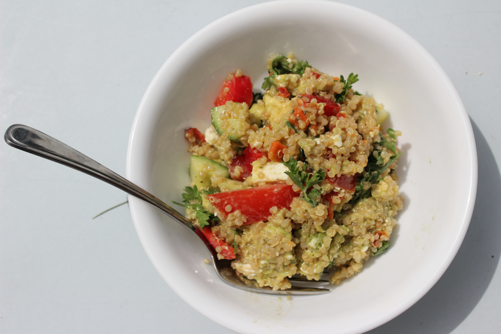 Avocado and Greek Quinoa Salad with lemon dijon mustard dressing. Red peppers, tomatoes. avocado, quinoa, cucumber. Gluten free and dairy free options. Bowl and fork