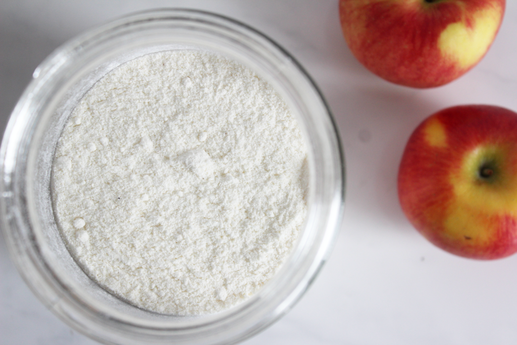 Container of flour with two red apples beside it