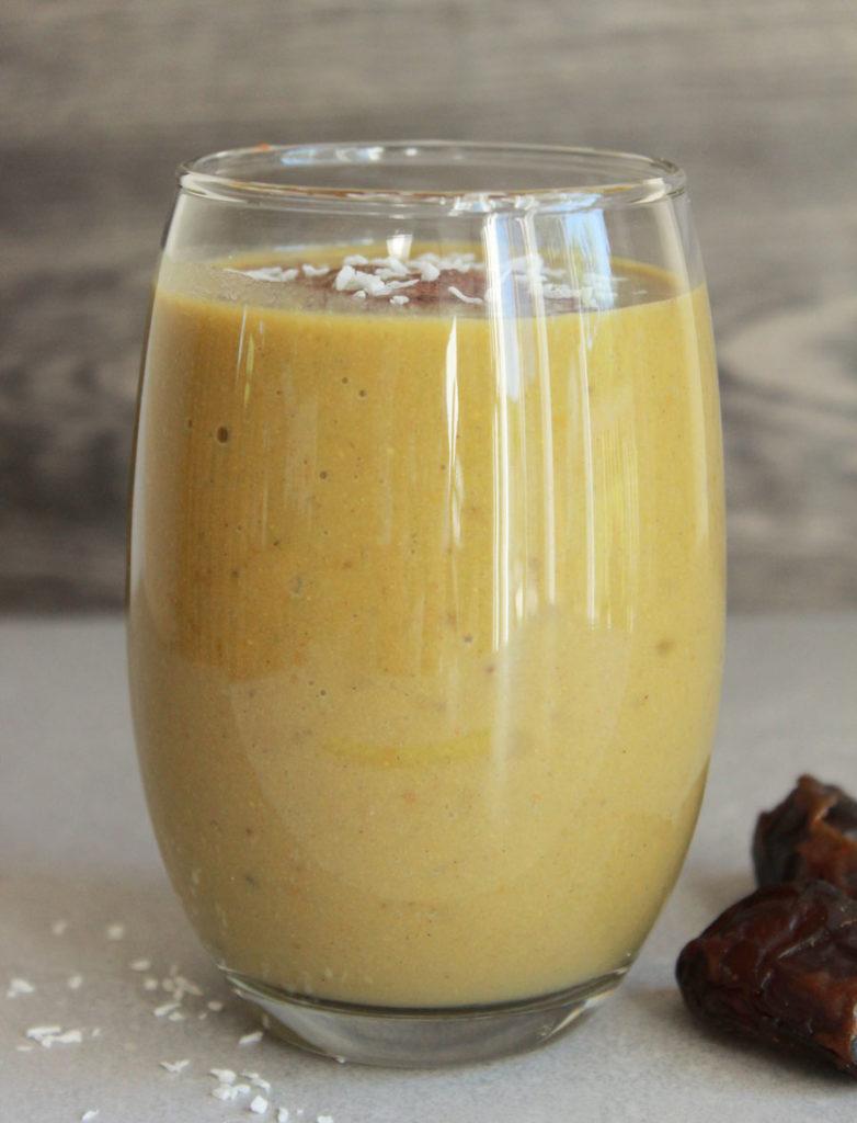 Vegan Pumpkin Pie Protein Smoothie; tall glass yellow drink, medjool dates surrounding