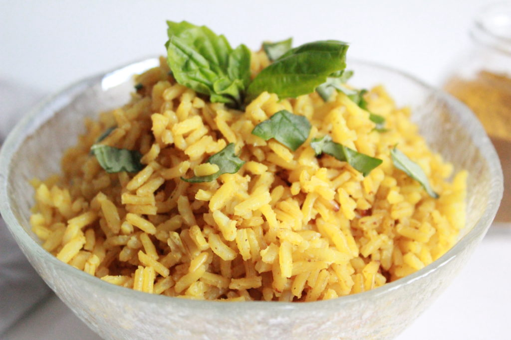 Golden rice with Basil leaves in a bowl. Easy curry rice recipe.