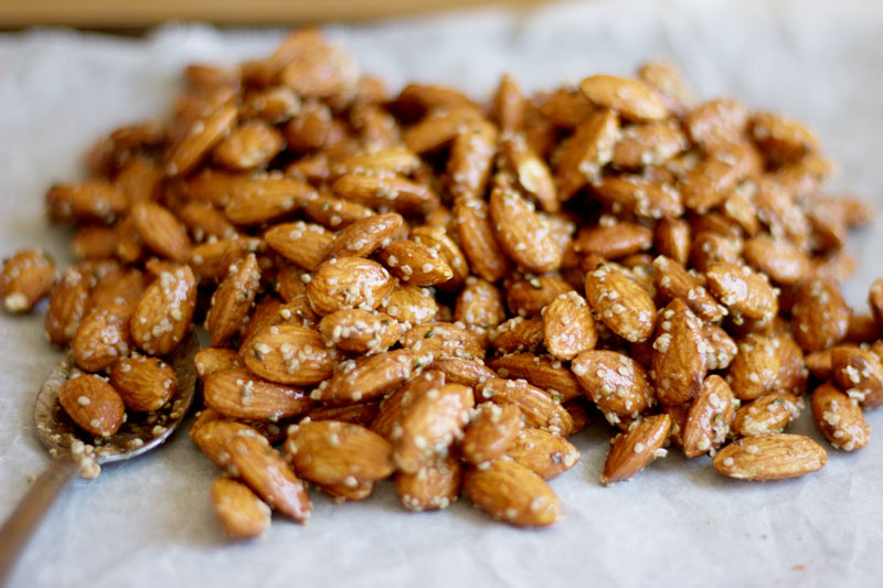 Pile of Honey and Hemp Roasted Almonds on parchment paper - A sweet healthy snack that is packed with natural protein. {Gluten Free & Dairy Free} www.nikkisplate.com