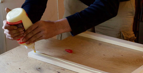 Applying wood glue to the pine strips