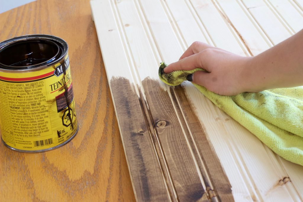 Use an old cloth to apply the wood stain to your wood photography background