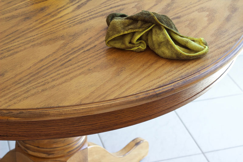 Use a rag to wipe the stain on the dining room table, following the wood grain