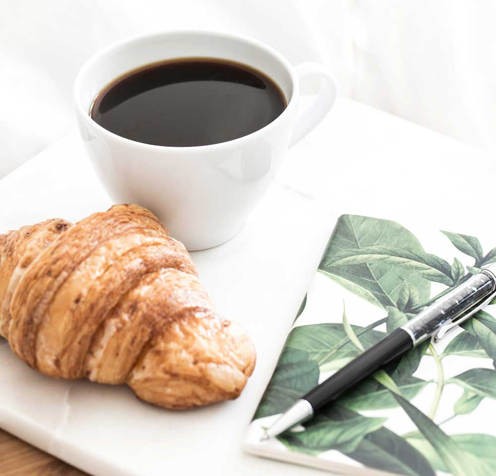 A cup of black coffee, a croissant, and a notebook and pen on a white plate