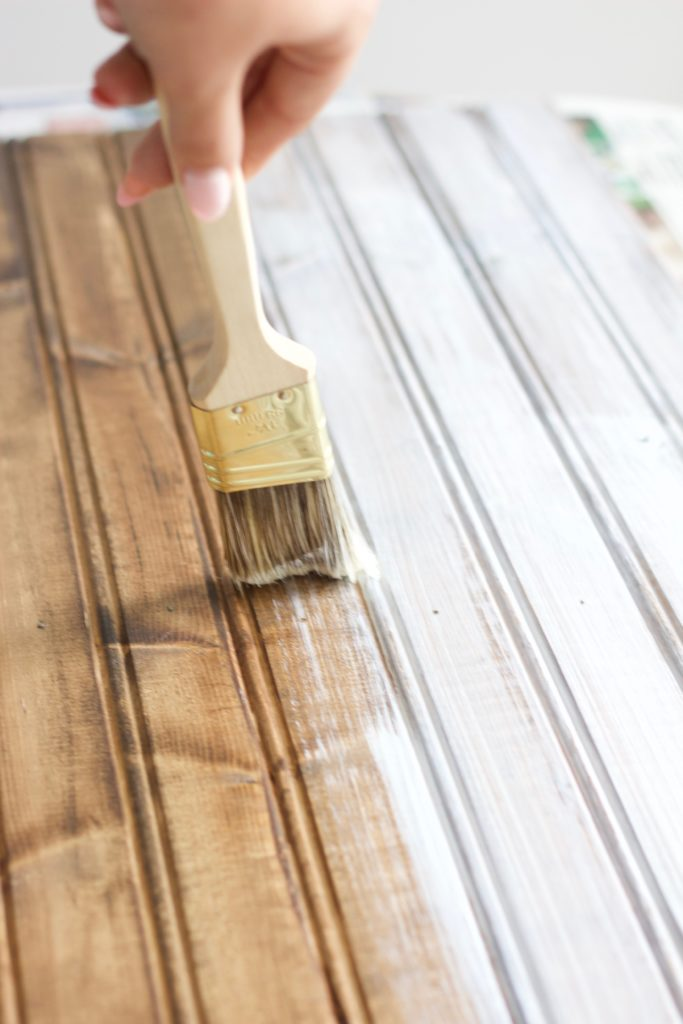 Use a very thin light layer of white paint over the wood stain to begin whitewashing