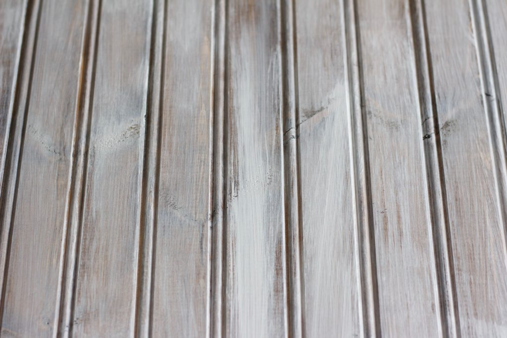 When whitewashing wood, you need to add a light layer of white paint with a few spots of more coverage