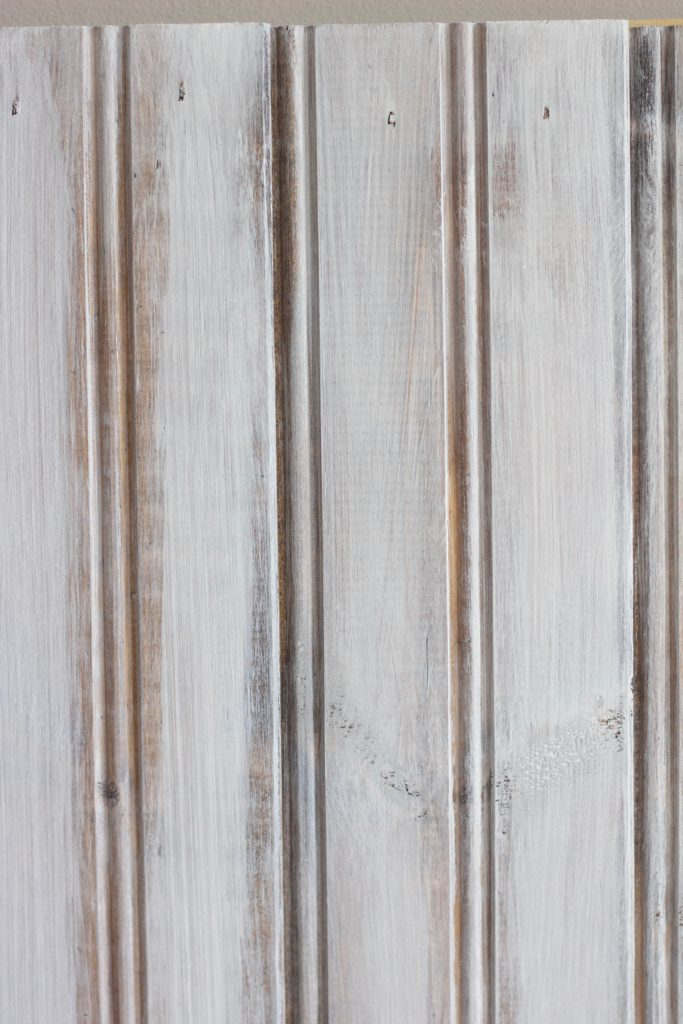 Sanding down the layer of white paint gives the piece of wood a whitewashed look