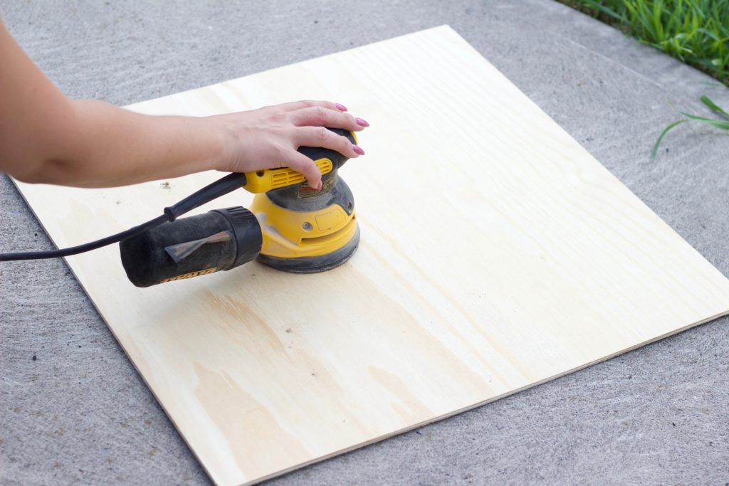 Sand down the plywood board with a handheld sander