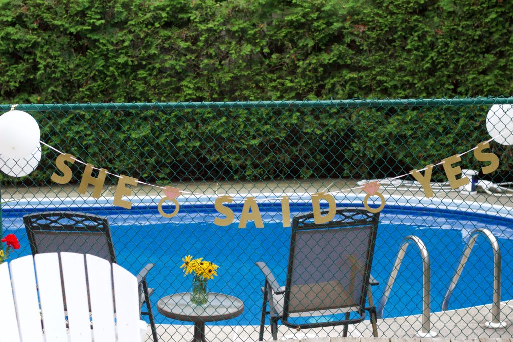 "Nikki's engagement party decor featured a ""She Said Yes"" banner hung on the fence near the pool."