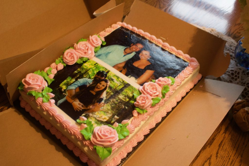 The lovely cake for Nikki and Dylan's engagement party featured two pictures of the couple and pink roses