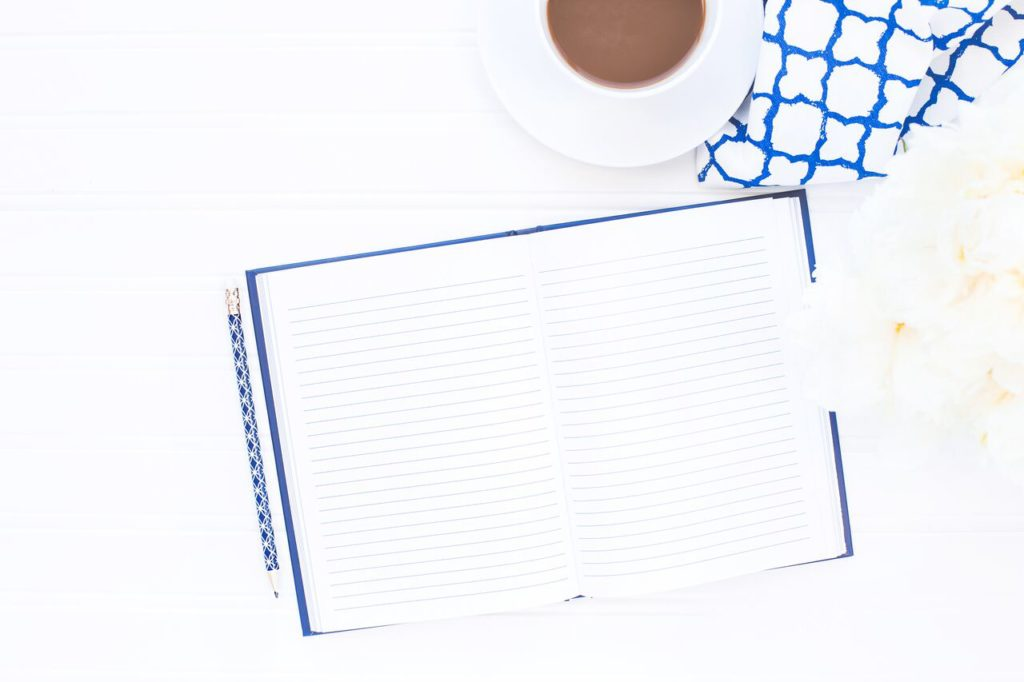 A notebook and pencil on a table with flowers and a cup of coffee