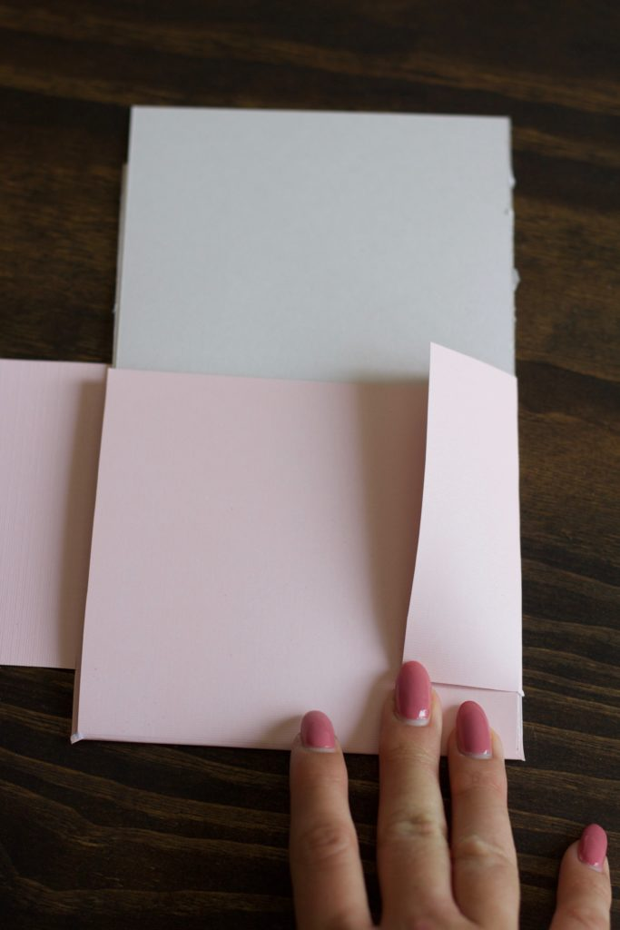 Folding pink cardstock to make a small folder to hold my bridesmaid proposal info cards