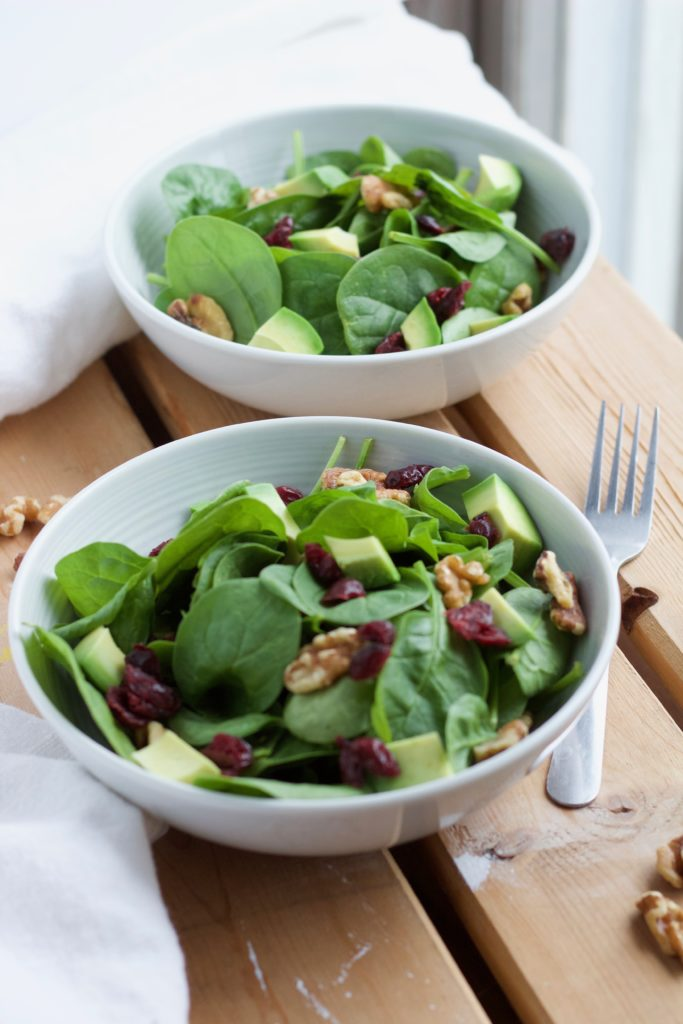 This fresh cranberry walnut salad is made with crisp spinach, apples, and topped with a honey ginger dressing