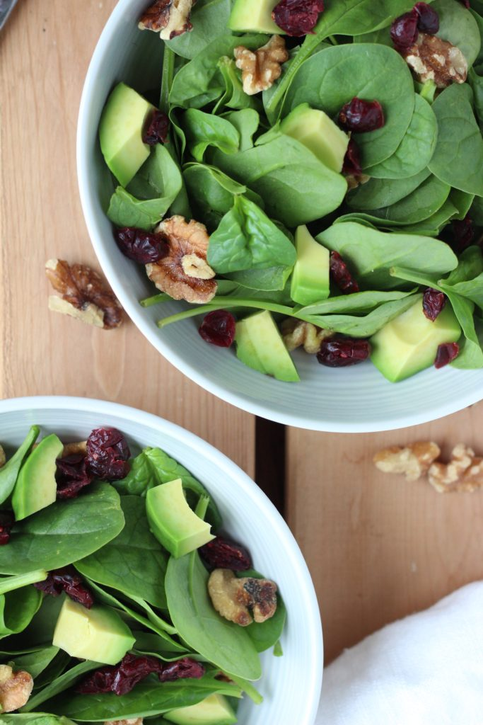 This cranberry walnut salad is topped with fresh avocado and a sweet and tangy honey ginger dressing