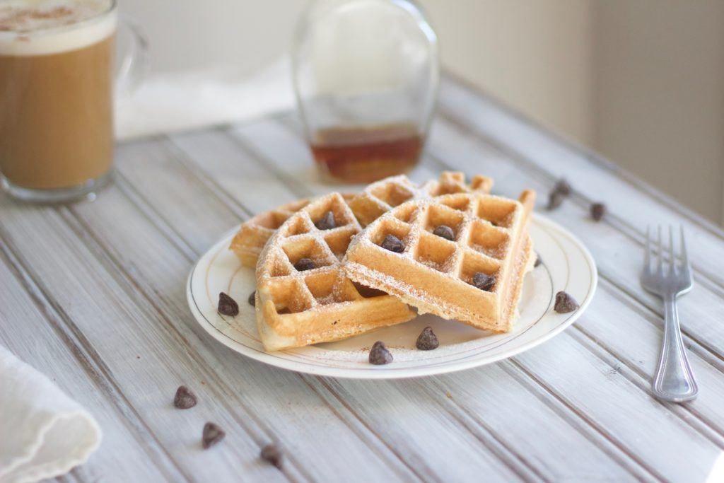 Homemade dairy free waffles topped with chocolate chips and dusted with powdered sugar