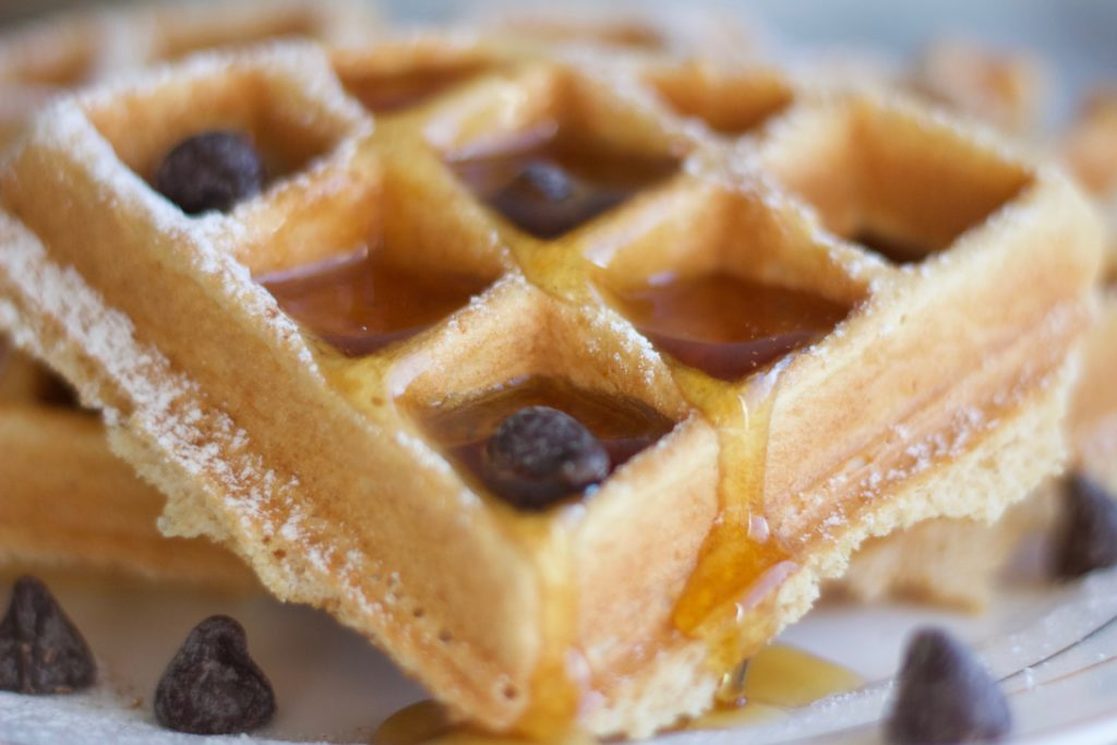 Gluten Free and Dairy Free Belgian Waffles topped with maple syrup and vegan chocolate chips