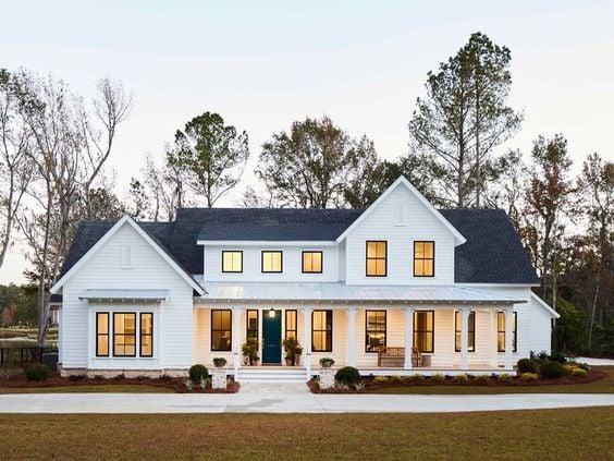 The black window trim on this all-white farmhouse style house exterior makes the windows pop!