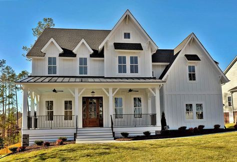 This farmhouse style home is so classic and clean with a mostly white exterior and black trim accents