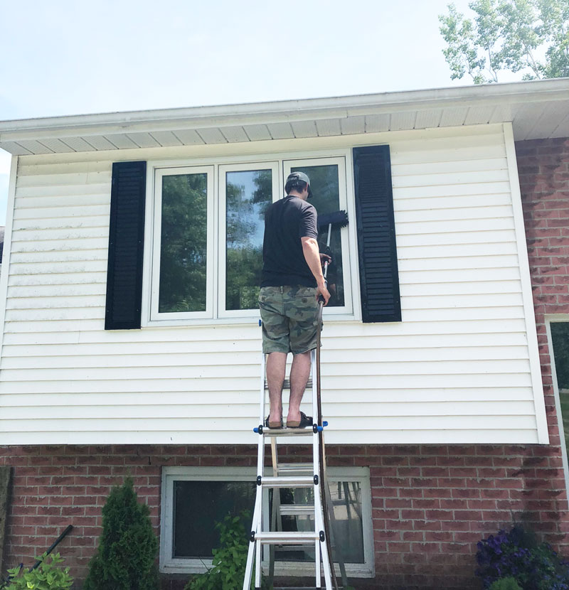 Dylan cleaning the windows after cleaning the vinyl siding on our home