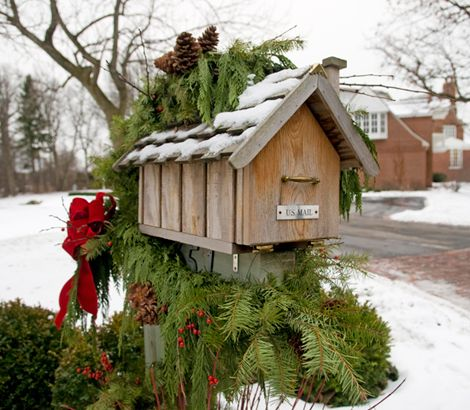 This snow-covered Christmas mailbox is decked out with fresh pine tree branches, pine cones, and bright holly berries