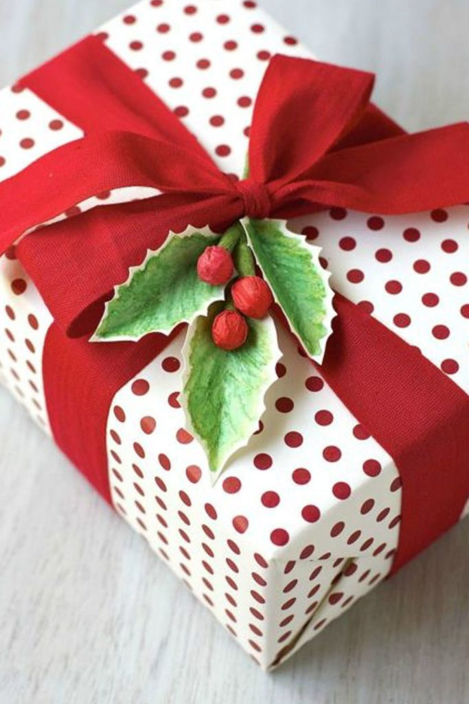 This gift wrap is colorful red and white polka dots, with red ribbon and holly berries.