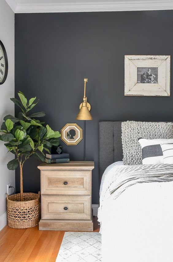 The dark grey accent wall in this master bedroom is echoed in grey linens and decor.