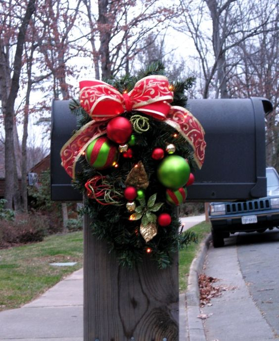 This Christmas mailbox is simple and festive with a red bow and wreath donned with Christmas ornamments