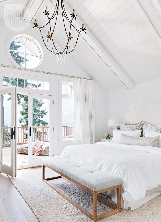 This grand master bedroom is a cozy getaway, with high shiplap ceilings and private deck