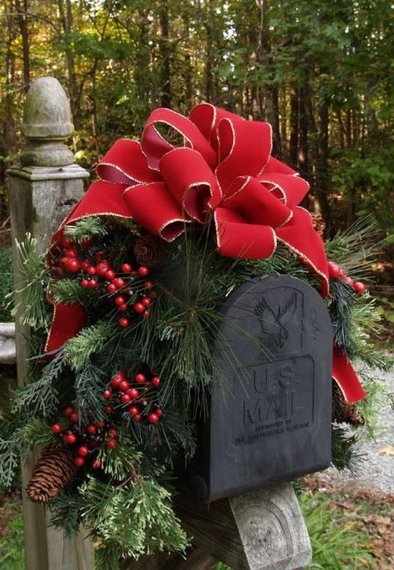 This Christmas mailbox is decked out with a giant red bow, hollie berries, and beautiful pine branches