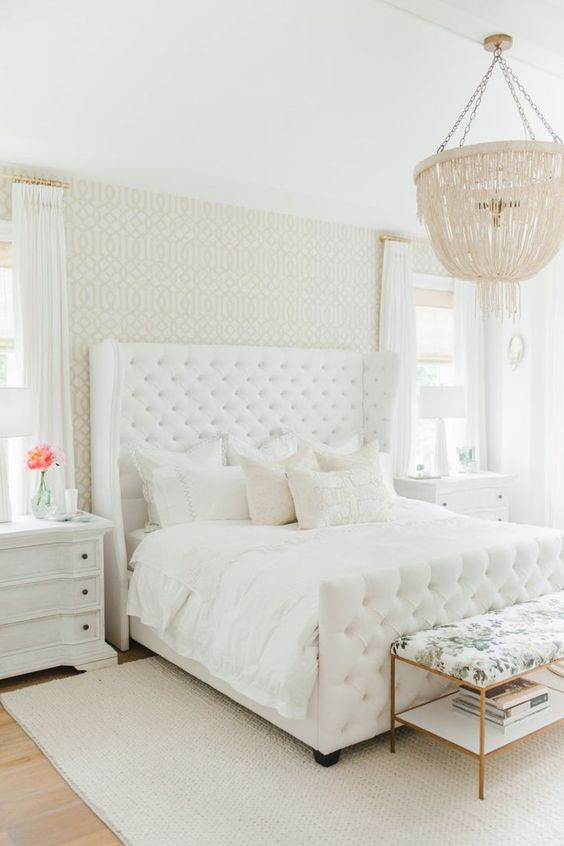 I love the subtle femininity of this master bedroom. The patterned wallpaper, upholstered headboard, and crystal light fixture are all great features