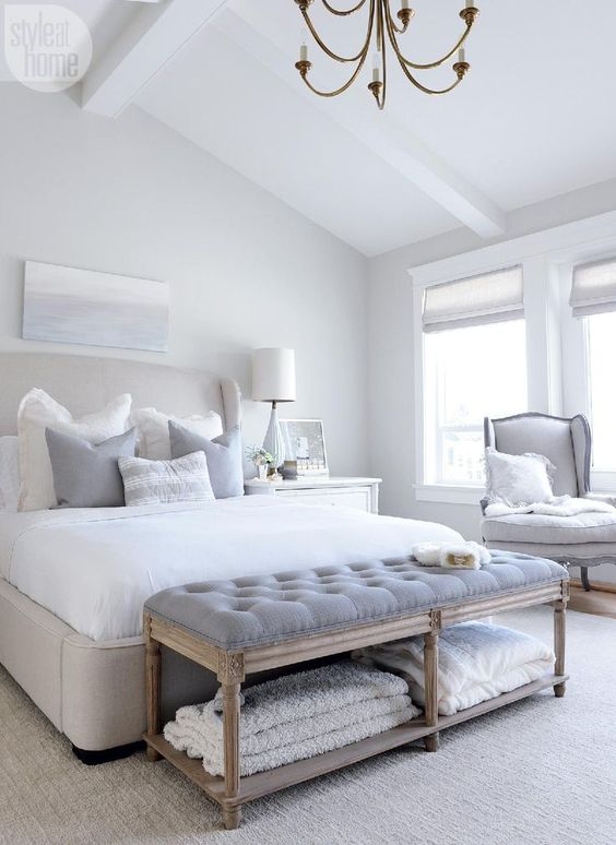 This bright white master bedroom mixes a neutral color scheme with cozy antique furniture for style and comfort