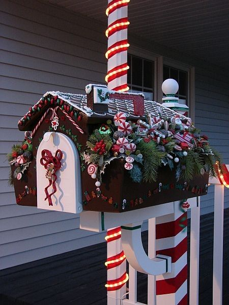 This Christmas mailbox is decorated like a gingerbread house, complete with candy pieces, frosting snow, and a candy cane pole