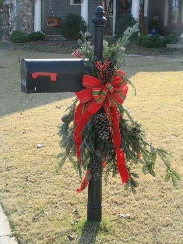 This Christmas mailbox has pine tree leaves complete with snowy pine cones and a large red and green plaid bow