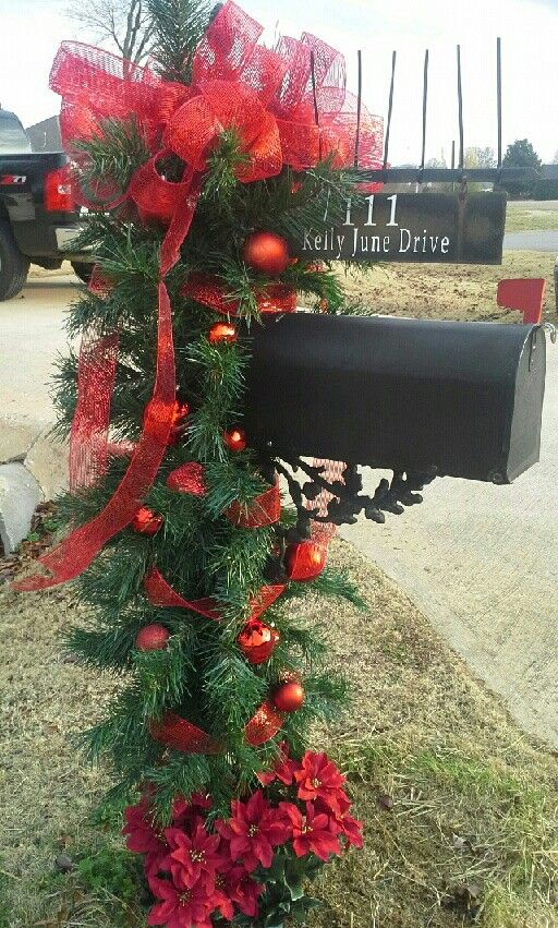 This Christmas mailbox is decked from top to bottom with fresh balsam branches, bright red ornaments and a big red bow