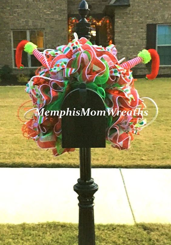 This whimsical Christmas mailbox is covered with colorful ribbon and topped with upside down elf legs!