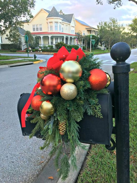 This Christmas mailbox has a large red bow, some bright and shiny Christmas ornaments, and fresh pine tree branches