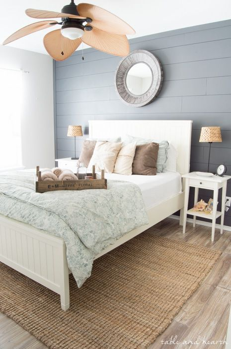 I love the tropical vibe of this master bedroom. The shiplap accent wall, and the large panel fan are statement features