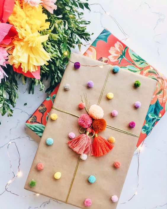 The colorful pom poms on this simple gift wrapping gives this present so much personality