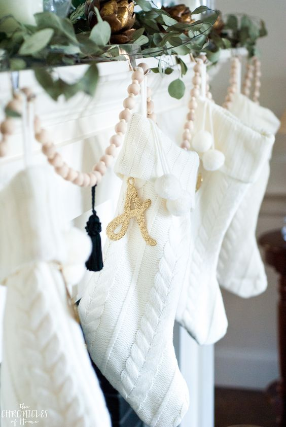 I love these white knit stockings wkith gold letters, hung on a simple green and gold Christmas mantel
