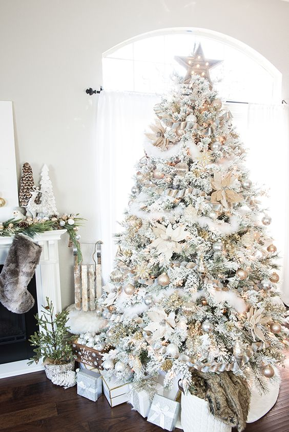 This white and gold Christmas tree has stars, garland, and even fake snow!