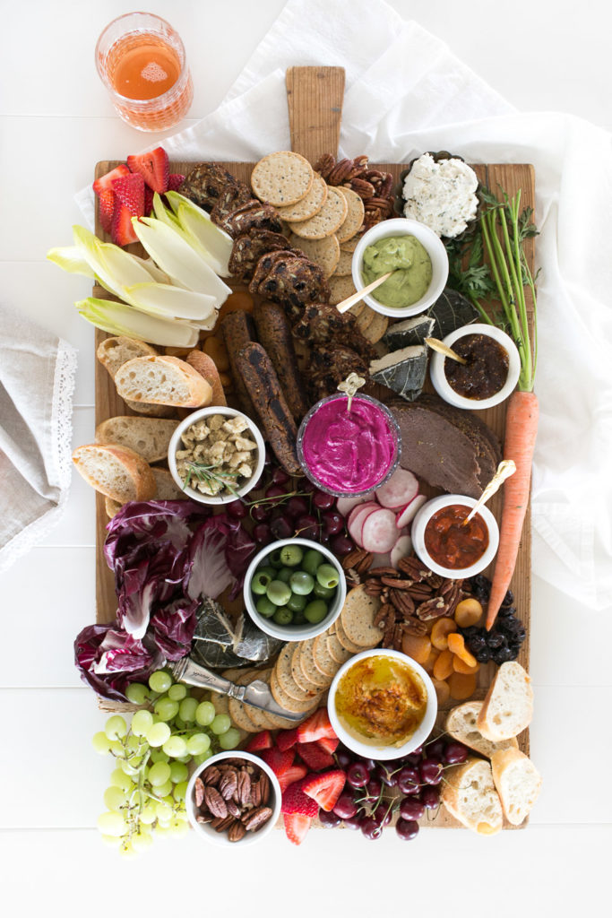 this vegan charcuterie board is packed with color from fresh fruits and veggies, along with plenty of dips and bread