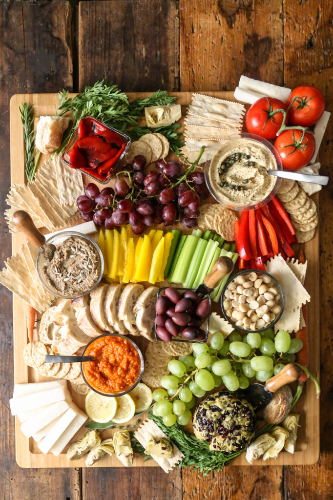 this vegan charcuterie board focuses on different crackers and crisp, colorful veggies and nuts