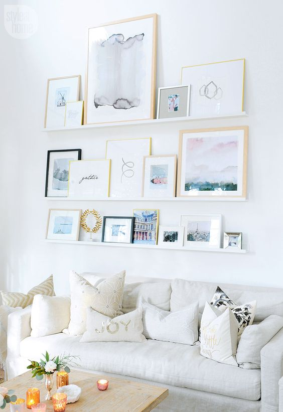 """I love how all the images on this gallery """"wall"""" are propped up on shelves! The artwork and different size frames really makes this a great focal piece in the room."""