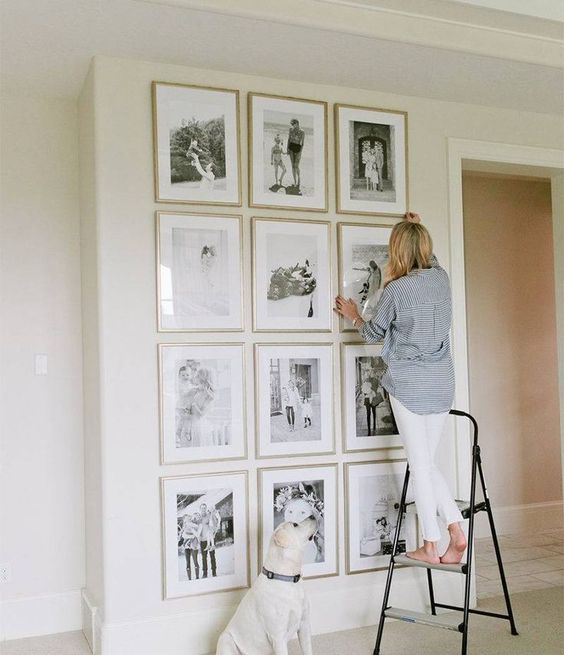 This full-wall gallery wall is a great accent, with slim gold picture frames and black and white pictures