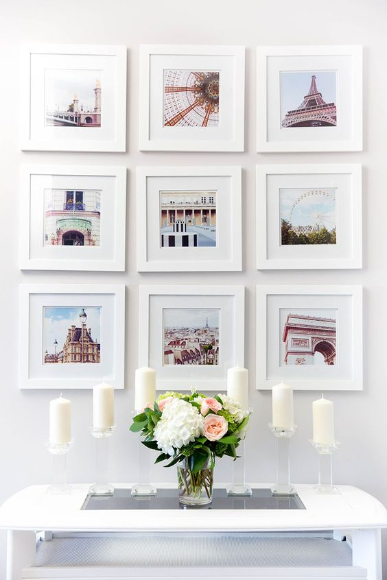 This gallery wall has bright color pictures of famous landmarks, all in simple white picture frames