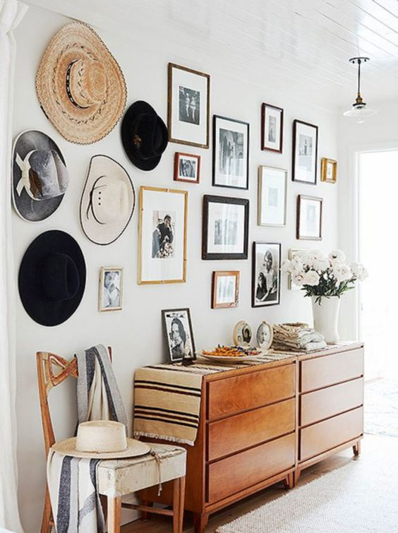 This gallery wall displays not only pictures, but hats too! This gallery wall is a great representation of family and personal style, with different picture frames and different size pictures.