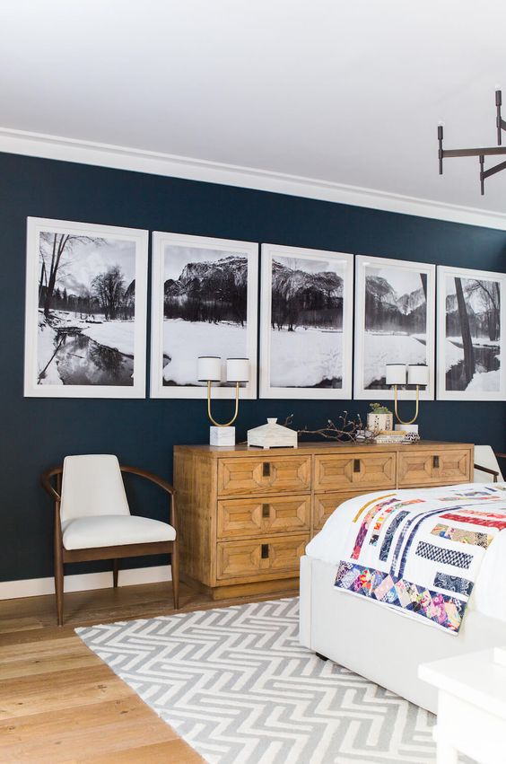 This large gallery wall is such a beautiful statement piece against the dark blue wall! I love the panoramic photography broken up into five frames