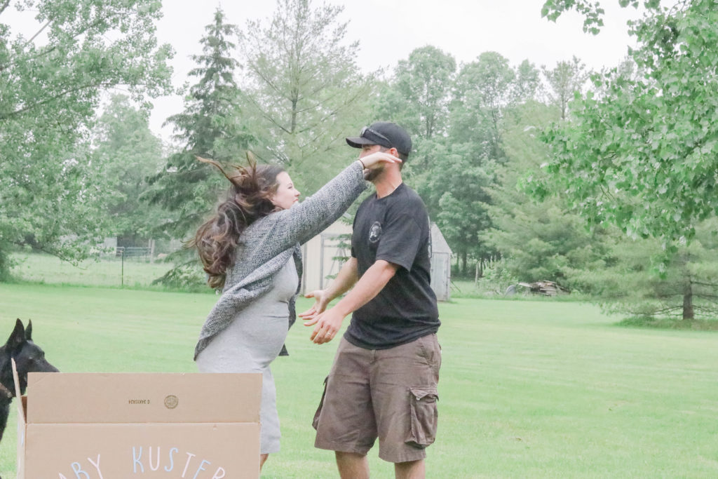 Gender Reveal Party - mom and dad to be reaching for a hug