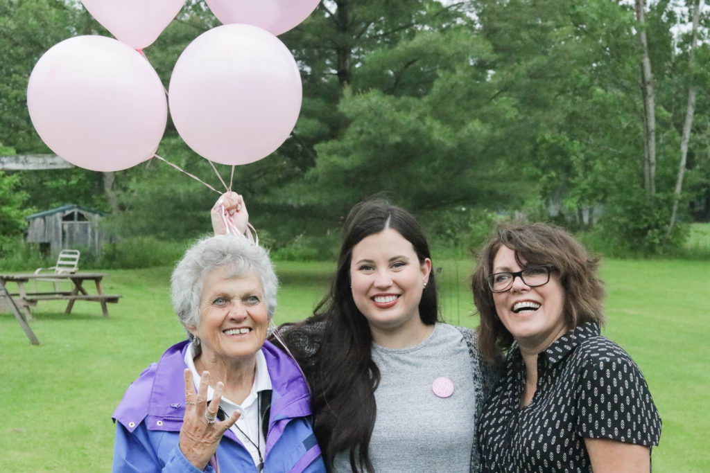 Gender Reveal Party - three generations of women holding pink balloons, excited to have the fourth girl to be added.
